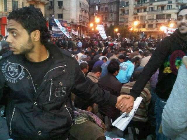 Slavná momentka zEgypta roku 2011 -- koptští křesťané chrání modlící semuslimské spoludemonstranty před policií. Foto Nevine Zakiová