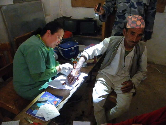 Neuroložka Maya zKáthmandú, nyní univerzální polní lékařka aneúnavná aktivistka dobrovolnické pomoci. V improvizované ordinaci vpobořené škole zašívá roztrženou ruku. Foto archiv J. Piňose aP. Hrdličkové