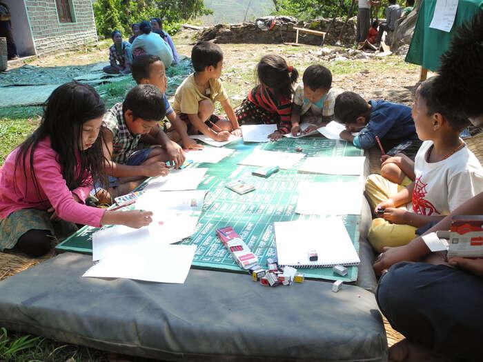 Děti vMesipě kreslí namatraci zpobořeného zdravotního střediska a nautržené tabuli splánem vesnice. Bavilo jeto celý den vedru navzdory. Foto archiv J. Piňose aP. Hrdličkové