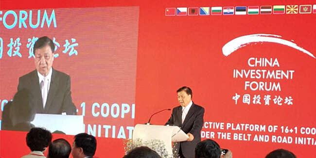 Člen stálého výboru politbyra ÚV KSČíny, jinak též šéf čínské ideologie apropagandy, drží řeč naČínském ekonomickém fóru vPraze. Text zajeho zády dokládá, jak seakce, původně předkládaná veřejnosti jako záležitost čistého byznysu stala integrální součástí čínské politiky vůči postkomunistickým zemím. Repro DR