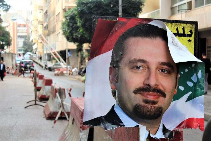 Z části stržený politický plakát stváří  Saada Harírího alibanonskou vlajkou vpozadí. Foto archiv The Turban Times