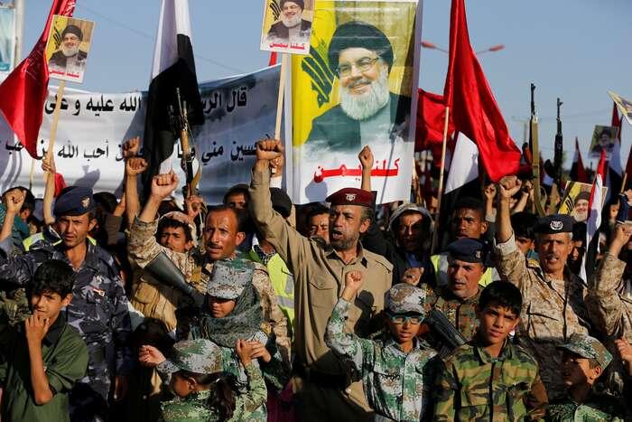 Ozbrojenci Hizballáhu amládež hnutí najedné zdemonstrací. Vpozadí natransparentech tvář Hassana Nasralláha, nejvyššího představitele organizace vzemi. Foto archiv Mei.edu