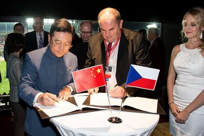 Chan Chauto, pravá ruka ztraceného čínského poradce prezidenta Zemana, aMiroslav Pelta podepisují smlouvu ospolupráci mezi FAČR aCEFC zapřítomnosti tehdejšího premiéra Sobotky, čínské velvyslankyně aJaroslava Tvrdíka. Vpozadí asistuje Jan Hamáček. Repro DR