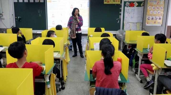 Děti naTchaj-wanu jsou během epidemii při výuce odděleny žlutými separátory. Tchaj-wan zvládá koronavirovou pandemii smnohem mírnějšími opatřeními as mnohem menšími počty obětí nežli evropské země. Jak jeto možné? Foto UNESCO
