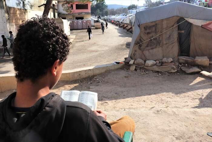 Muhammad, uprchlík zGazy, sepřed stanem naostrově Chios učí anglicky. Foto Michal Pavlásek