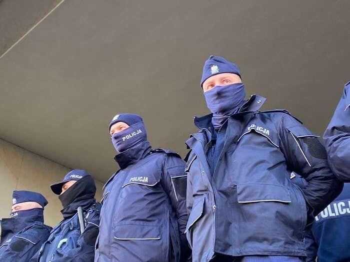 V elastických šedých rouškách snápisem Policja, obtékajících rysy policejních nosů artů, připomínají policisté masu Fantomasů. Foto Kateřina Spejchalová