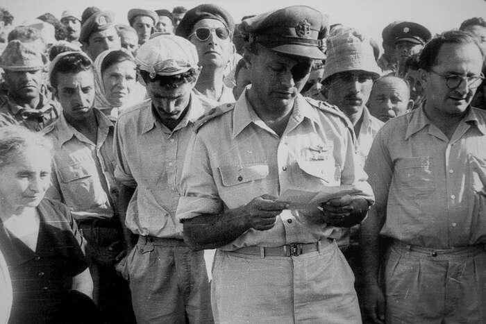 Moše Dajan čte smuteční řeč zaRoie Rotberga, kibuc Nachal Oz, duben 1956. Foto Twitter ProvMagazine