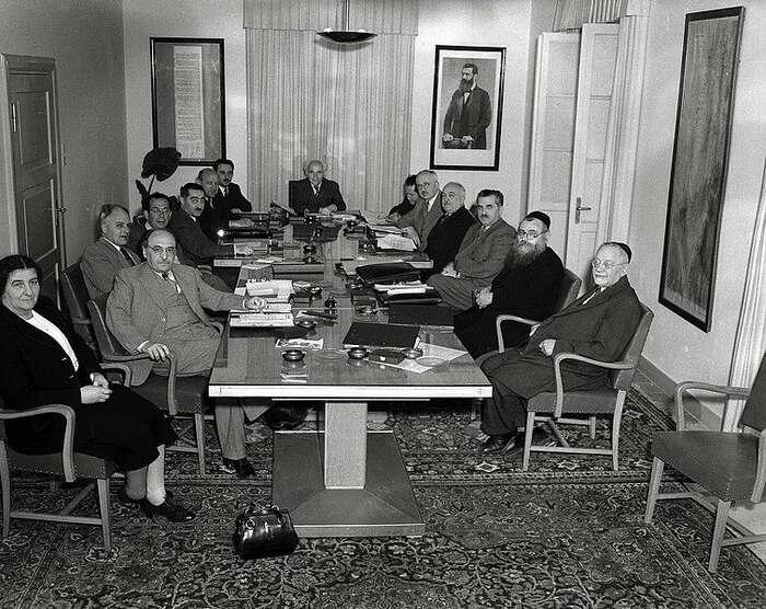 Moše Šaret usazený polevici prvního izraelského ministerského předsedy Davida Ben Guriona nafotografii zachycující první izraelský vládní kabinet vroce 1949. Foto WmC
