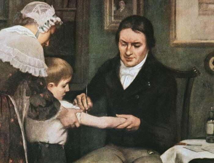 Edward Jenner očkuje osmiletého Jamese Phippse, olej naplátně Ernesta Boarda. Táž scéna jemimochodem vyobrazena pokaždé jinak. Existují iumělecká pojetí, vnichž chlapec vypadá vyděšeně akolem postávají lidé sezachmuřenými výrazy. Repro DR