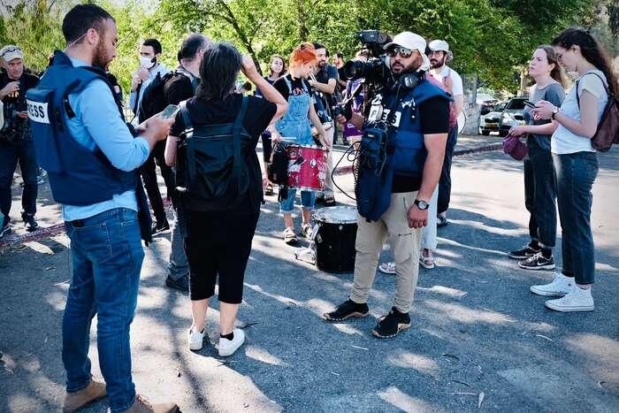 """Samotnému protestu sedostalo poměrně hodně pozornosti zestrany tisku. Někteří novináři přišli vneprůstřelných vestách. """"Ano, máme neprůstřelné vesty, protože včera tubyl osadník, který začal zničeho nic střílet nalidi."""" Foto Lucie Šarkadyová"""