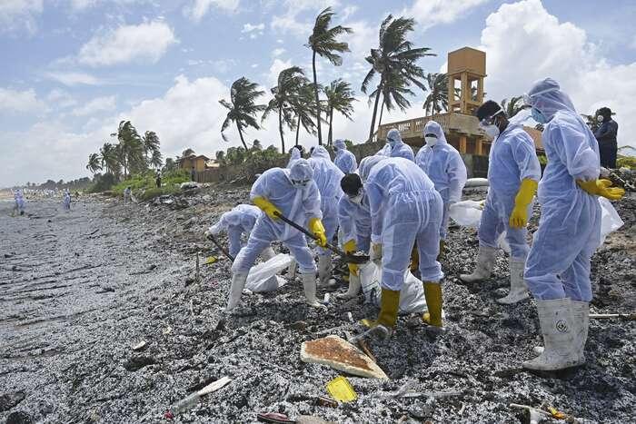 Následky znečištění moře apláží popožáru nákladní lodi odklízejí tisíce příslušníků námořnictva. Vochranných oblecích odstraňují šedivou vrstvu mikroplastů, která pokryla pláže nazápadním pobřeží Srí Lanky, zejména vokolí největšího města Colomba. Foto Lakruwan Wanniarachchi, AFP
