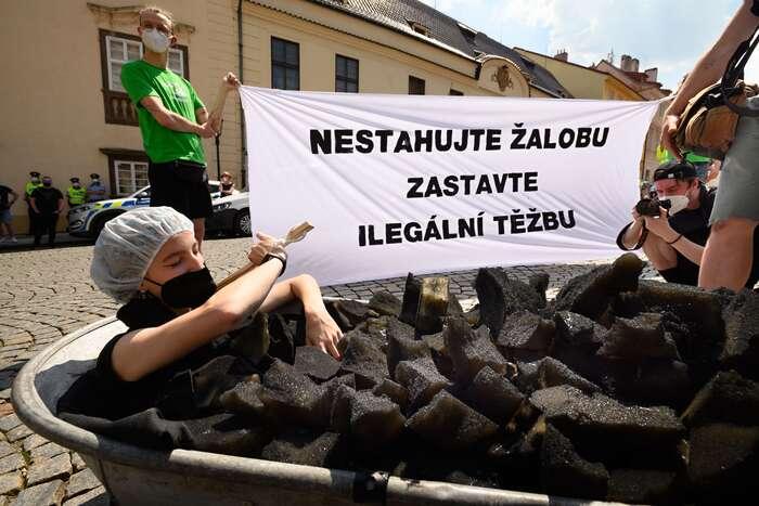 Před jednáním vlády uspořádala protest ekologická organizace Greenpeace. Jeho účastníci plnili skleněné nádoby avanu materiálem připomínajícím uhlí, aby upozornili, že pokračující těžba tohoto fosilního paliva vpolském dole Turów vodu mizející zpohraničních vesnic nenahradí. Foto Karel Šuster, Greenpeace